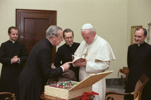 """Blessed Álvaro del Portillo, following a Polish custom on the feast of St. Nicholas de Bari, presenting some simple gifts to the recently elected Pope St. John Paul II. Msgr. del Portillo, commented that it was """"a kind gesture that children would have for their father""""."""